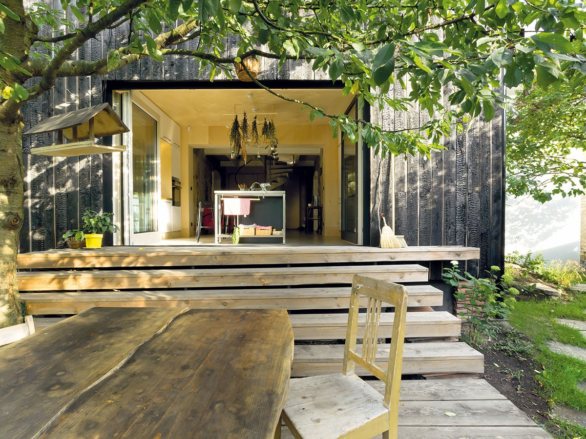 """Obzvlášť příjemné jsou části domu, jež komunikují s exteriérem – momenty, kdy dům prorůstá do zahrady a naopak. Dřevěná terasa se stolem zmasivu je """"zastřešena"""" větvemi třešně. FOTO DAVID MAŠTÁLKA (A1 ARCHITECTS)"""