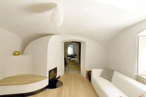 Obývací pokoj skachlovými kamny, knihovnou apohodlnou sedačkou − to vše se zabydlelo pod klenutým stropem. Takhle vidí moderní podobu tradiční obytné místnosti vateliéru A1Architects. FOTO DAVID MAŠTÁLKA (A1 ARCHITECTS)