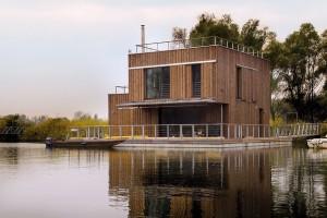 Plovoucí dům je s břehem spojen prostřednictvím můstku, vzpěry a lan, které stabilizují jeho polohu vůči břehu. V zábradlí na terase jsou vrátka, která umožňují nastoupit na člun ukotvený přímo k terase. FOTO EXWORKS