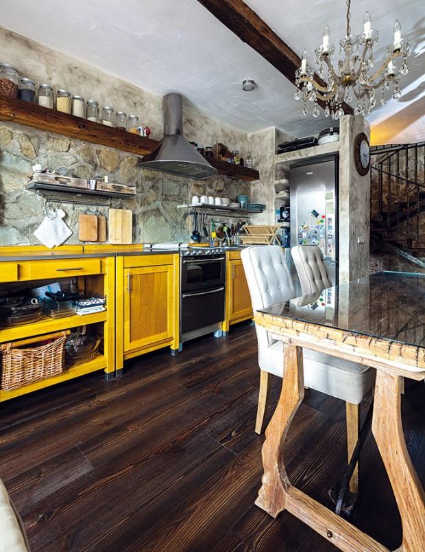 Přímá kuchyňská linka svyzděným prostorem na chladničku, vyrobená ze světlého masivu se žlutým nádechem, kontrastuje s ostatním, převážně tmavým dřevem. Kuchyňskou zástěnu tvoří obklad zpískovce, který najdete i u schodiště nebo vkoupelně. FOTO DANO VESELSKÝ