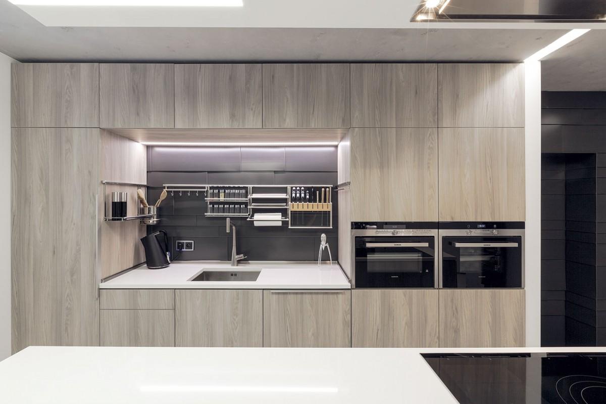 Kuchyňská linka je stejně jako ostatní nábytek vbytě vyrobená na míru, všechno sjednocuje materiál astyl. Dvířka zjasanové dýhy doplnil architekt pracovními plochami zbílého kamene akontrastní zástěnou zgrafitově šedých titanzinkových šablon. Stejný obklad je ina stěně ana vstupních dveřích. FOTO DANO VESELSKÝ