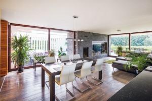 Jídelní aobývací část navazuje na kuchyň. Vládnou tu šedá sedací souprava azelené doplňky. Útulný dojem pak dotvářejí zejména zelené pokojové rostliny. FOTO JAKUB HOLAS