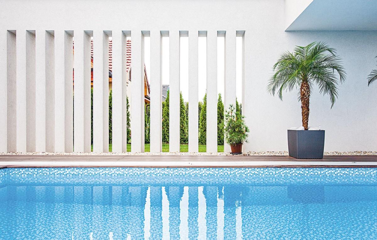 Působivé průřezy sgeometrickou estetikou vnášejí do atria světlo, hru stínů azároveň vytvářejí na hladině bazénu zajímavý efekt. Přitom zachovávají soukromí všech, kteří si teplé dny ve vodě užívají. FOTO JAKUB HOLAS