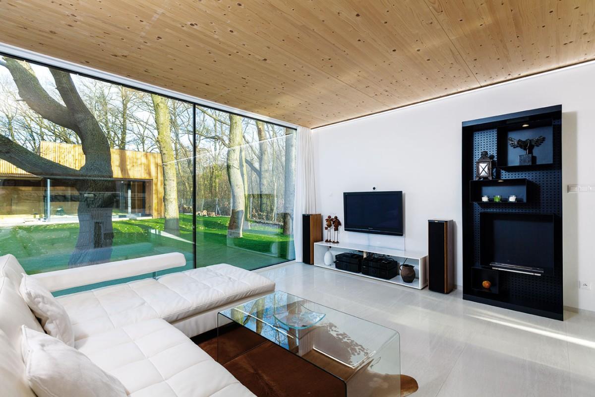 Dřevěný strop působí jako barevný imateriálový protipól kbílé podlaze zumělého kamene. Interiér tak získal teplejší vzhled. Foto Dano Veselský