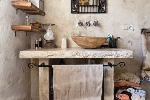 Centrální koupelna vpřízemí má podobně jako ta vposchodí přírodního ducha. Skříňky nahradil zděný stolek skameninovým umyvadlem. Jednoduché dřevěné police nabízejí prostor na nezbytnosti, ručníky jsou stylově srolované vproutěných koších. FOTO DANO VESELSKÝ