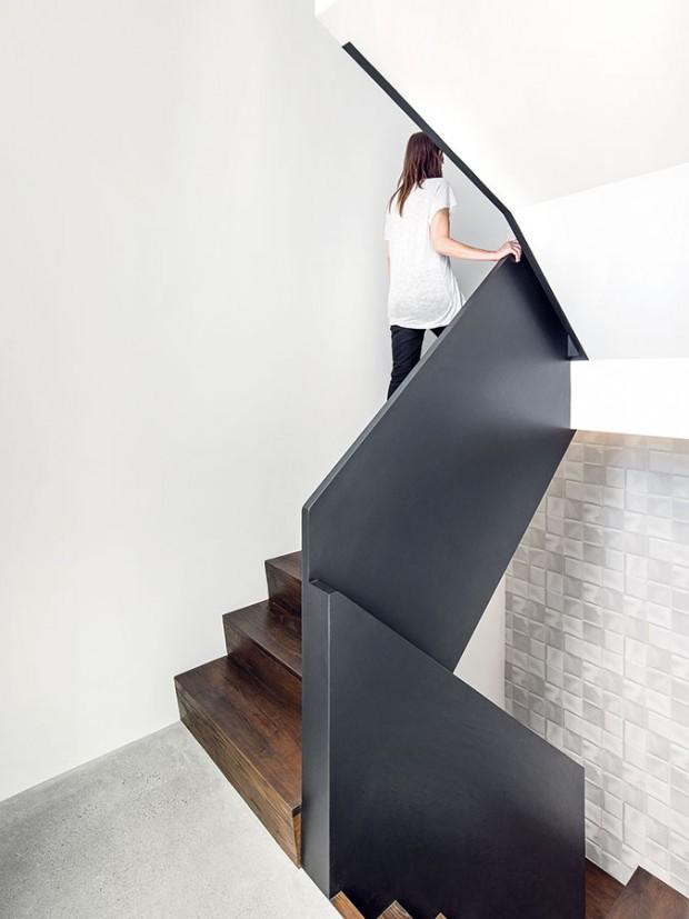 Centrální schodiště. Na schody bylo použito stejné dřevo vtotožné úpravě jako na kuchyňský nábytek, zábradlí odkazuje na tmavě šedý keramický obklad, který můžeme najít v koupelně. FOTO ADRIAN WILLIAMS