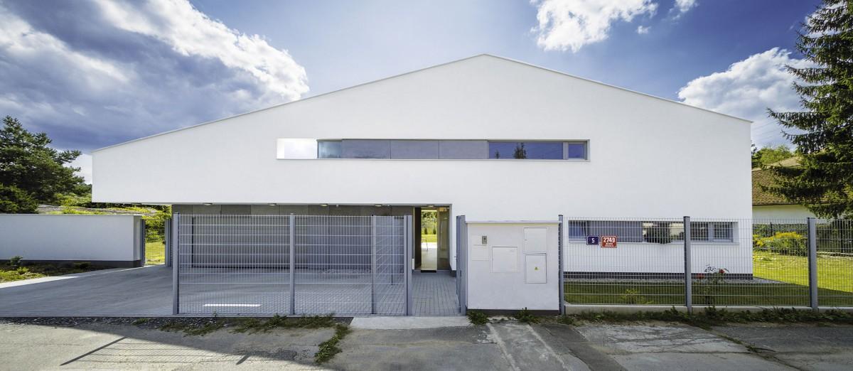 Zpohledu od ulice působí dům trochu jako kosmická loď. Architekti vytvořili chytrý a působivý kompromis mezi přáním majitele (chtěl plochou střechu) a požadavkem úřadů (trvaly na sedlové). FOTO IVAN BÁRTA