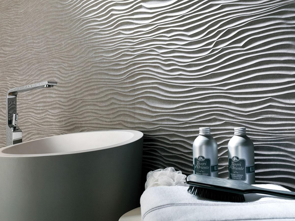 Plastické stěny. Hlavním trendem budou letos velkoformátové rektifikované 3D obklady v tlumených odstínech béžové, šedé a bílé. Trend imitací přírodních materiálů vládne i zde. FOTO KOUPELNY STEFANO