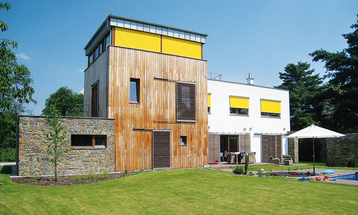 Vhodnou kombinací stínicích systémů lze nejen zabezpečit pohodu vinteriéru, ale iefektně oživit architekturu domu. Okenice skovovým rámem adřevěnou naklápěcí lamelou jsou zde zkombinovány svýraznými žlutými screenovými roletami. foto VOIVO