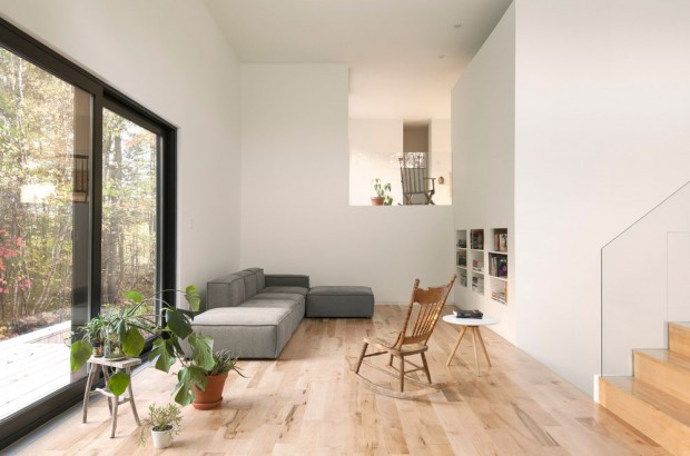 Vpravo od schodiště je umístěn obývací kout, jehož dominantu tvoří bílý monolitický blok sahající až do nejvyšší, třetí úrovně. Niky v něm slouží jako knihovna. Foto: Maxime Brouillet