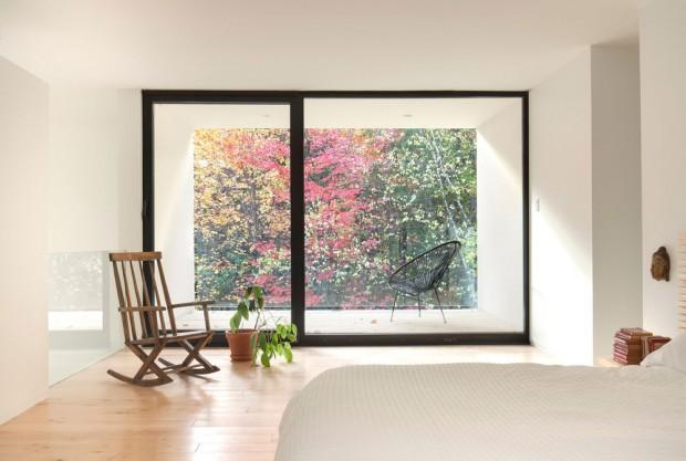 Na druhém konci ústí ložnice francouzským oknem do otevřené lodžie s půvabným výhledem do korun stromů, jemuž nebrání nic, ani zábradlí. Místo něj použili architekti jednoduše jen tabuli z čirého skla. Foto: Maxime Brouillet