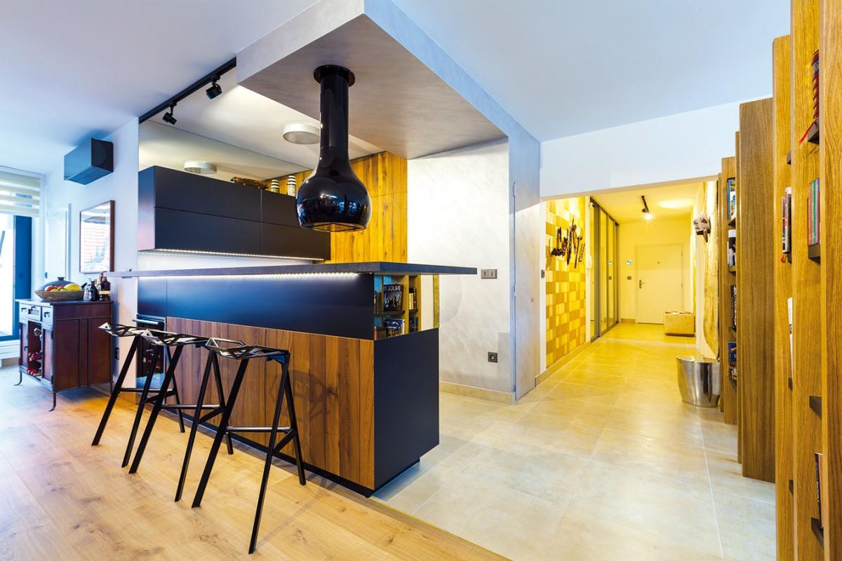 """Poloha kuchyně byla v dispozici bytu od začátku jasně daná. Příjemná kombinace masivního, jemně rustikálního dubového dřeva a elegantních hladkých černých ploch zapadla do celkové """"moderně exotické"""" koncepce. FOTO DANO VESELSKÝ"""