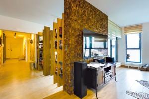Staré vnovém. Zakomponovat do nového interiéru několik dřevěných skříněk zpředcházejícího bytu byl jeden zúkolů pro autora interiéru. Za atypickou knihovnou je rafinovaně ukrytá pracovna, přes kterou se prochází na terasu. FOTO DANO VESELSKÝ