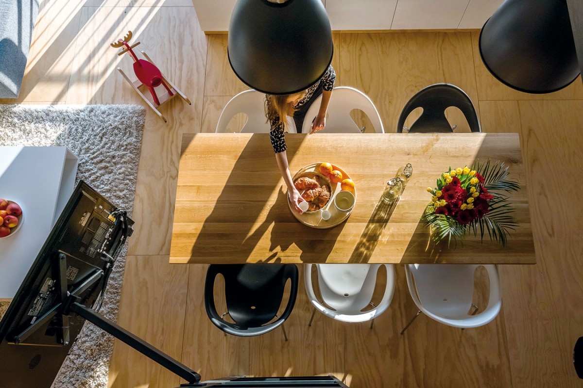 Kuchyňský stůl zmasivu má záměrně tmavší odstín, aby vprostoru převzal dominantní roli.