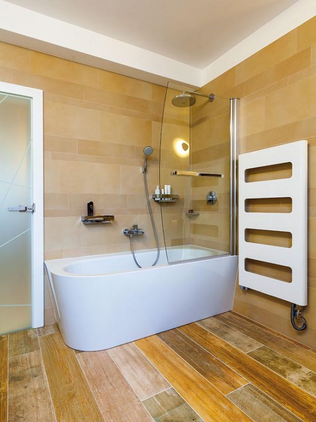 Koupelna získala při rekonstrukci víc prostoru a vlastní okno. Denní světlo, které se z ní přes skleněné dveře dostává do dlouhé chodby, působí v jinak tmavém prostoru velmi příjemně. FOTO DANO VESELSKÝ