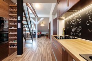 Žíhaná laminátová podlaha předurčila podobu většiny vybavení. Odstíny vní obsažené inspirovaly architektky ke hře sdřevěnými dekory.
