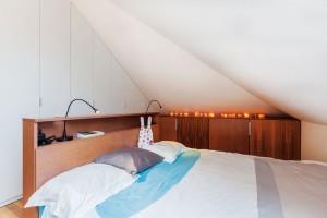 Ikdyž ložnice pod střechou prostorem zrovna neoplývá, šikovným architektkám se sem vešly dvě nízké komody po celé délce jedné ze šikmin astejně tak klasická ložnicová vestavná skříň.