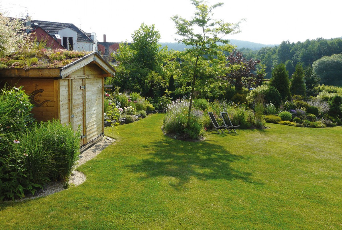Zterasy je krásný výhled na zahradní domek se zelenou střechou.