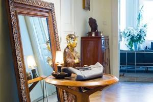 """Socha chrámového """"vítače"""" zVietnamu tematicky zaujala místo vpředsíni. Zátiší doplňuje starožitné zrcadlo zIndie ačeský """"retro"""" stolek, který zachránila Monika ze sklepa. FOTO JAROSLAV KVÍZ"""