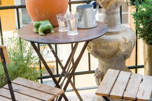 Malý balkon obrácený do tichého vnitrobloku zařídili Monika a Michael v provensálském stylu. Kamenný sloup koupený v Saint Remy de Provence skombinovali s jednoduchým sezením z jejich obchodu. FOTO JAROSLAV KVÍZ