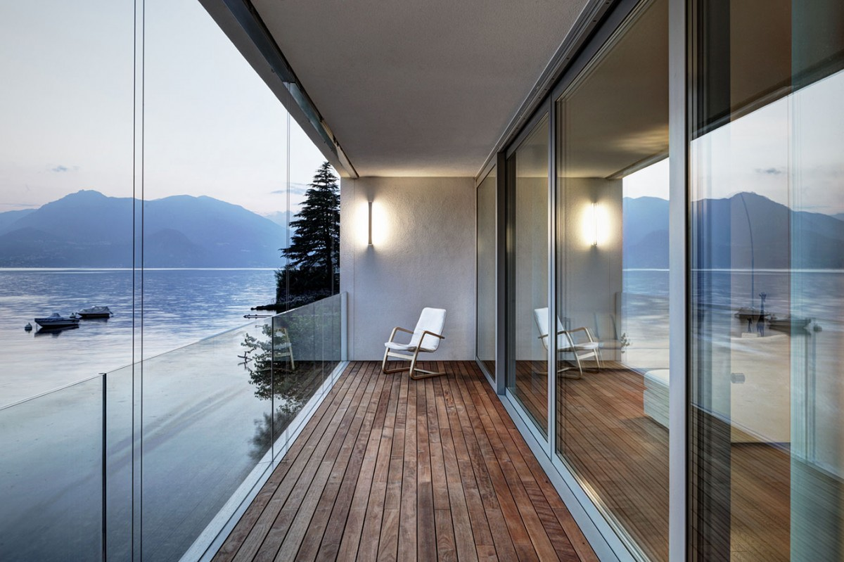 Balkonové zábradlí sestavené ze čtyř bezrámových bezpečnostních skel reflektuje členění posuvné stěny a poskytuje nerušený výhled na jezero