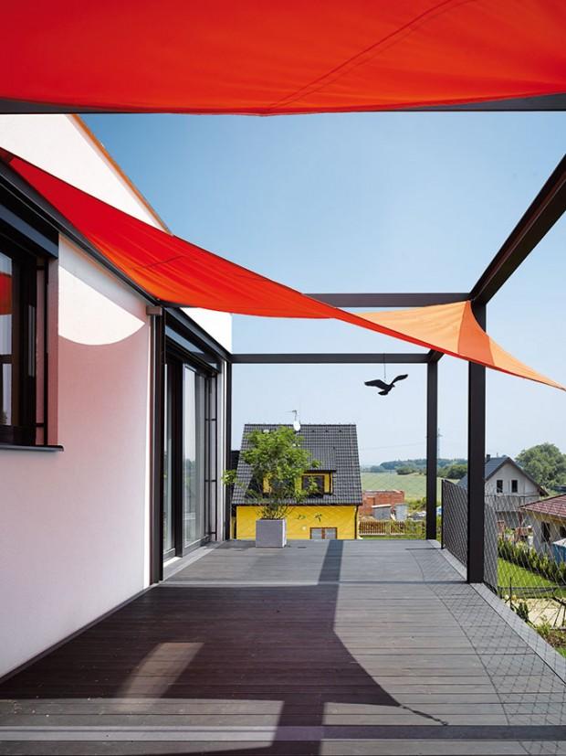 Velkorysá terasa vytváří kryté stání pro auta – otepelný komfort vhorním patře se starají kontrastně zbarvené plachty. FOTO FILIP ŠLAPAL