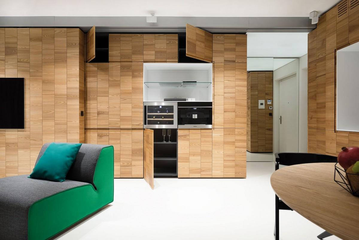 """Za dřevěným obkladem se většinou skrývají odkládací prostory – idíky otevírání bez úchytek (systémem """"push to open"""") nevypadají rušivě ani """"skříňovitě""""."""