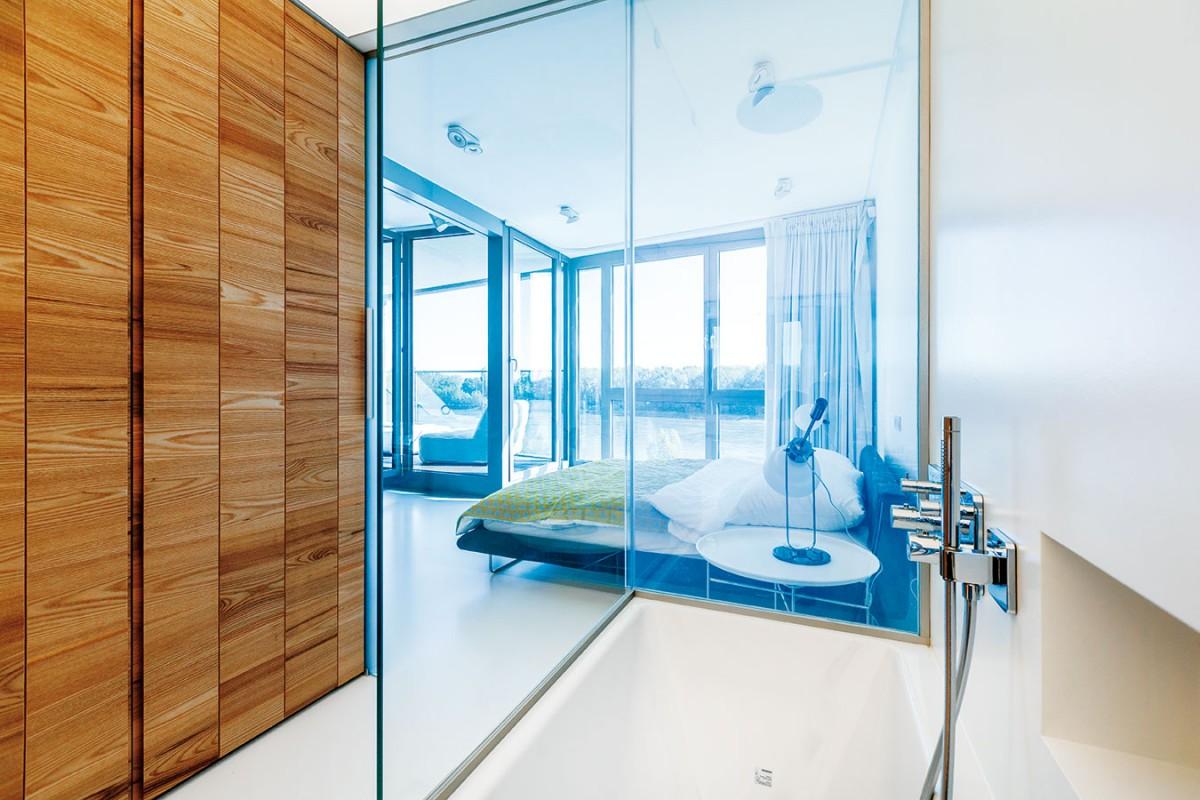 Hlavní úložné prostory ložnice umístili architekti do dřevěného boxu oddělujícího denní anoční zónu.