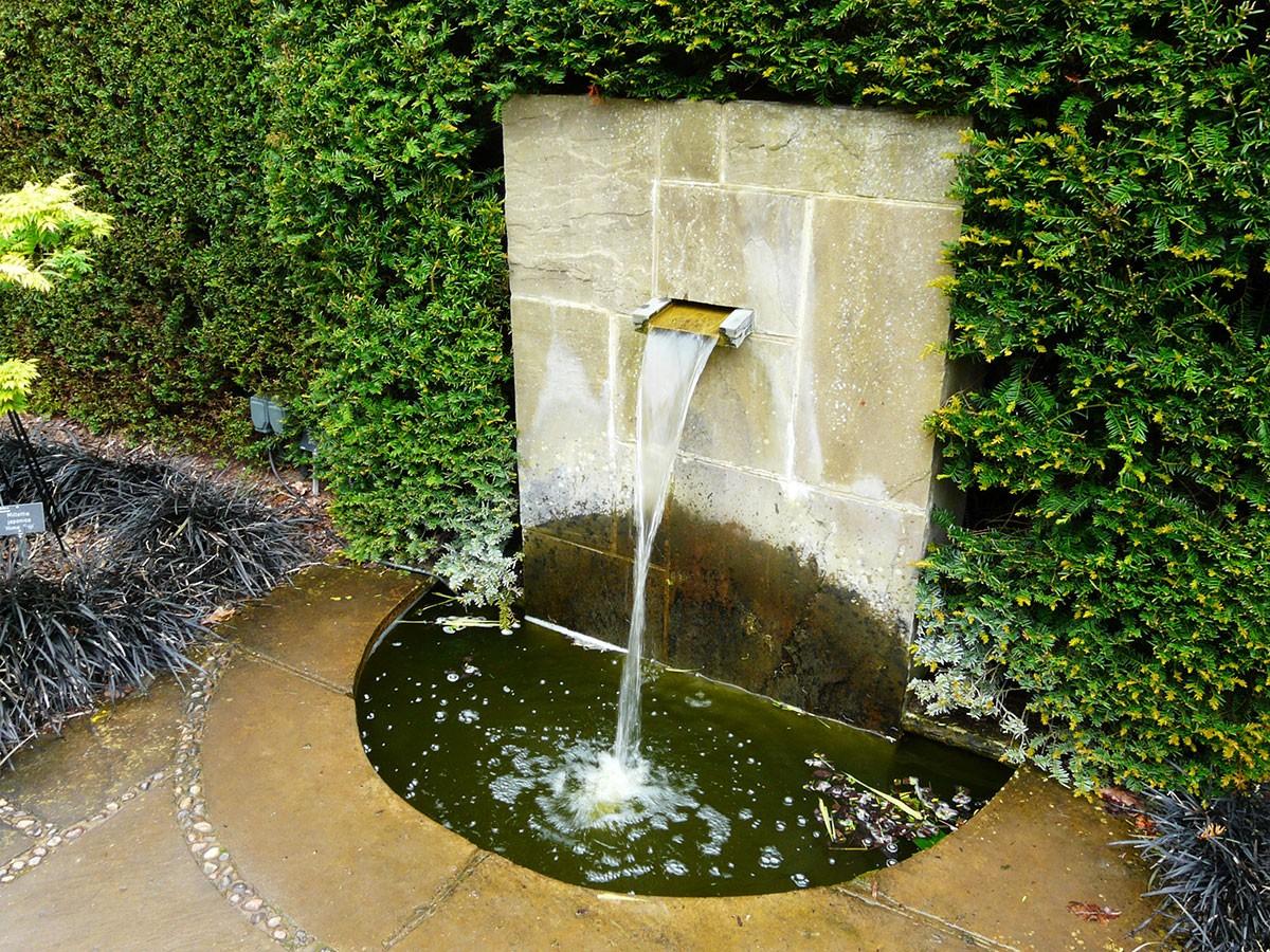 Klasicky vodní prvek s jednoduchým pozadím živého tisového plotu působí uklidňujícím dojmem. FOTO LUCIE PEUKERTOVÁ