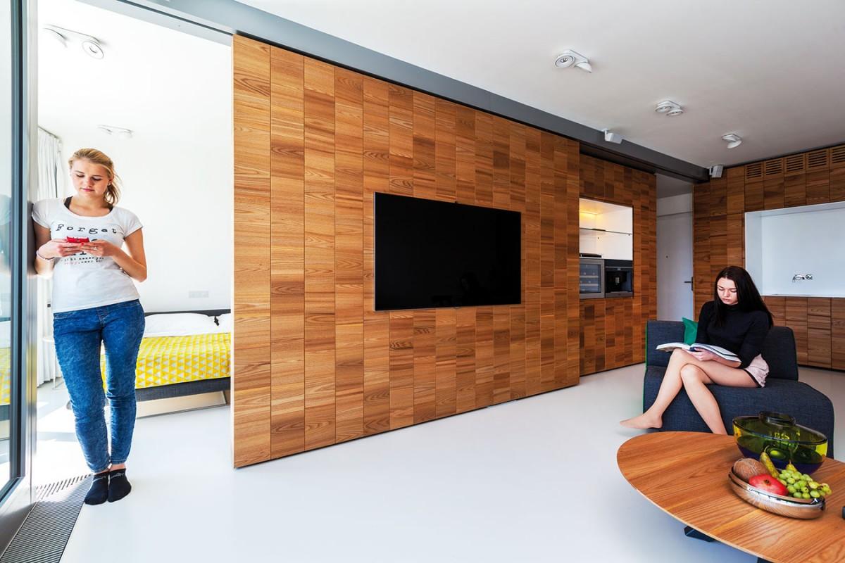 """""""Denní varianta"""" – ložnice se pomocí posuvné stěny úplně uzavře. Dispozice pak odpovídá běžným denním prostorům, na jaké jsme zvyklí – obývací pokoj, kuchyň, jídelna."""