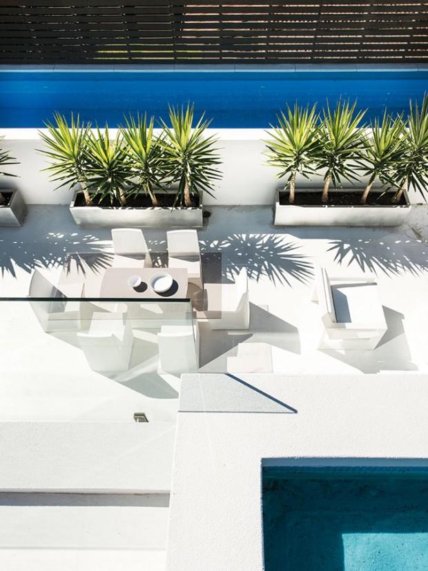 Hlavní terasa, orientovaná na sever, zptačí perspektivy. Jednolitou bílou plochu narušuje jen barevnost dřevěného plotu, vysazených rostlin aazurová modř bazénové vody. FOTO DMAX