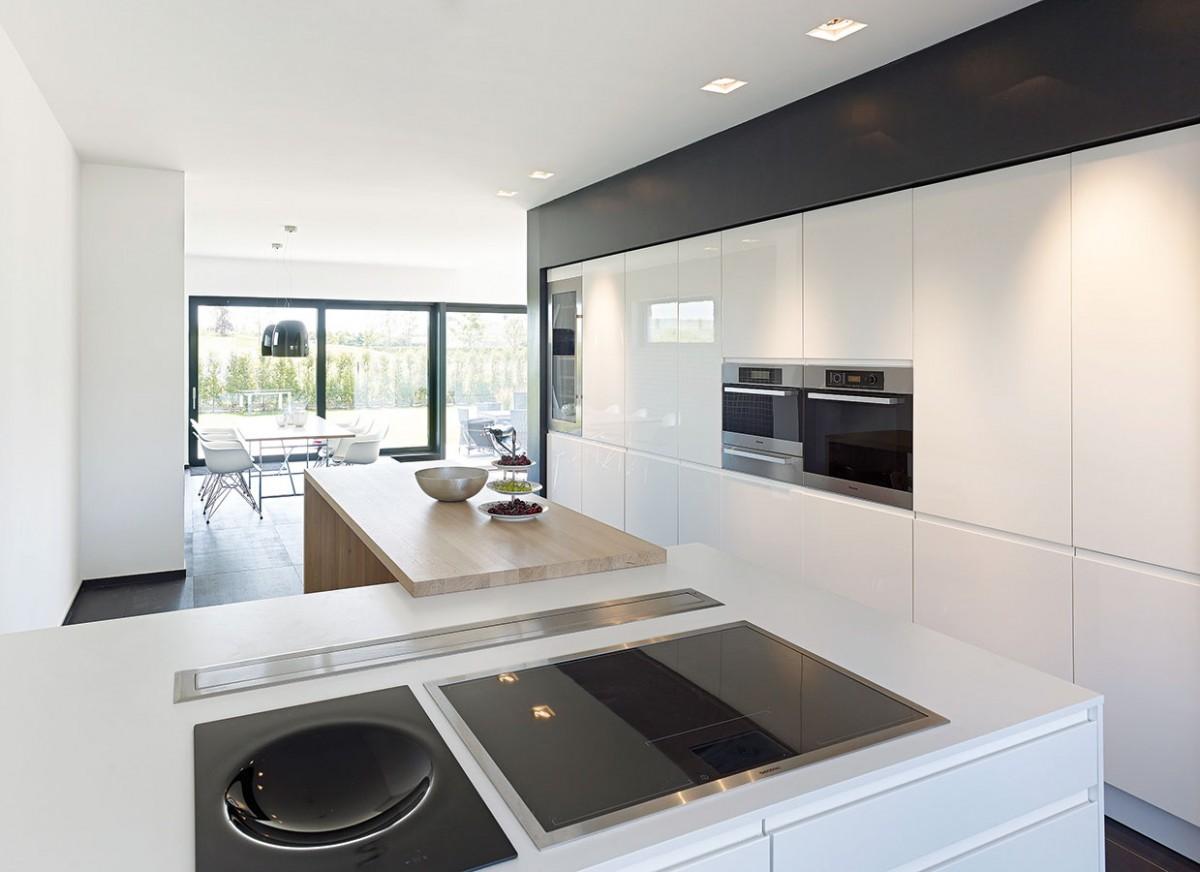 Kuchyň je otevřená a přirozeně navazuje na jídelnu a obývací prostor, oddělený od zbytku přízemí pouze různou výškou úrovní. Barevné řešení doplňují chromové spotřebiče. FOTO SCHÜCO CZ