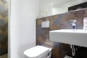 Prostor koupelny oživuje zvolený vícebarevný vzorovaný obklad stěn, který příjemně doplňuje bílou sanitu.