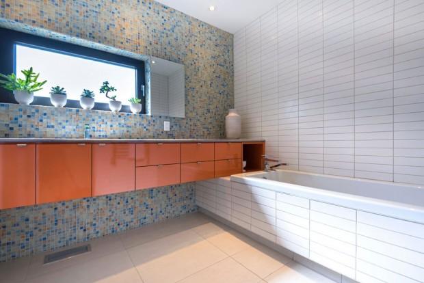 Koupelna je dle přání majitelů rozdělena na tři samostatné jednotky: umývací část s umyvadlovými skříňkami v konzolové variantě a vanou, a dále sprchový kout a toaletu. FOTO ALBERTO BISCARO