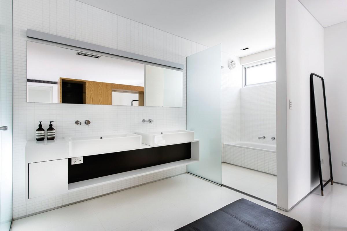 Vkoupelně aložnici se opakuje podobné barevné schéma jako například vkuchyňské části. Strohost černobílé opět zjemňují dřevěné prvky, tentokrát vpodobě velkého masivního bloku, který je díky pojetí koupelny en suite společný oběma prostorům. Vložnici plní funkci čela anočních stolků, vkoupelně poskytuje úložné prostory… FOTO DMAX