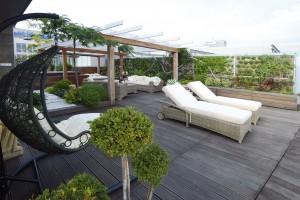 Na terase v nejvyšším podlaží navrhli architekti exoticky působící oázu odpočinku, jejíž rámec vytvořila zelená stěna.