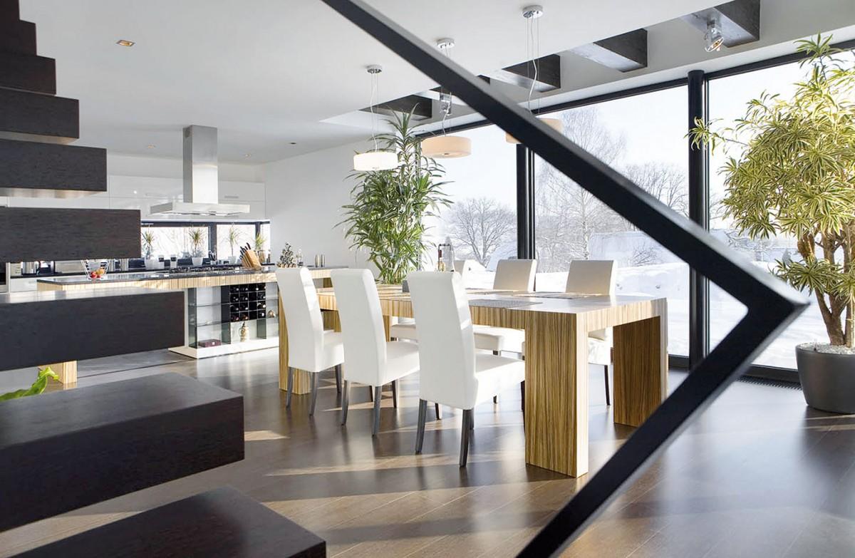 Hlavnímu obytnému prostoru dominuje velký jídelní stůl aminimalisticky pojaté schodiště.
