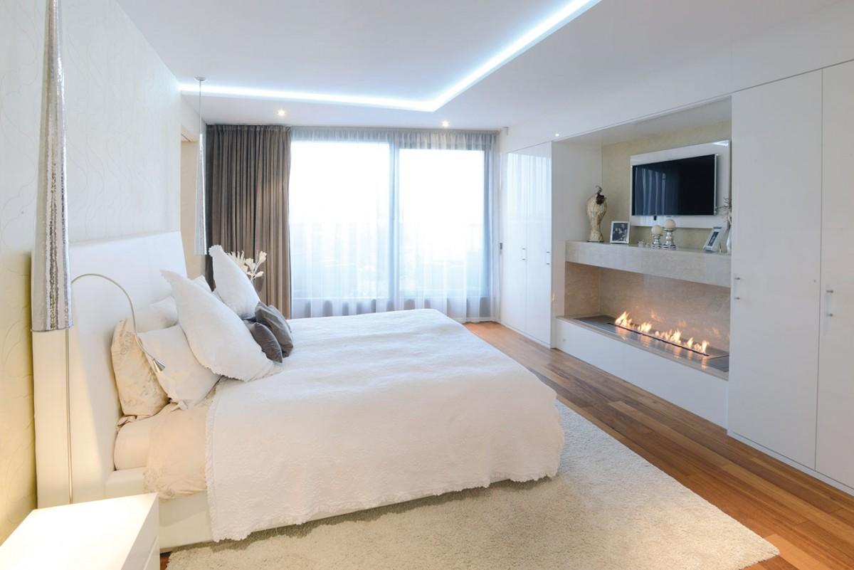 Vhlavní ložnici je naproti posteli kromě televize také krb na biolíh, který si majitelé nemohou vynachválit – vytváří totiž nejen uklidňující atmosféru, ale sálá zněj iteplo, příjemné především za chladných sychravých večerů. FOTO KOSI ARCHITEKTI