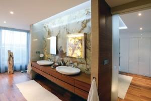 """Koupelna """"en suite"""". Na ložnici majitelů přímo navazuje elegantní prostorná koupelna. Dominuje jí týkové dřevo, které dobře odolává vodě. FOTO KOSI ARCHITEKTI"""