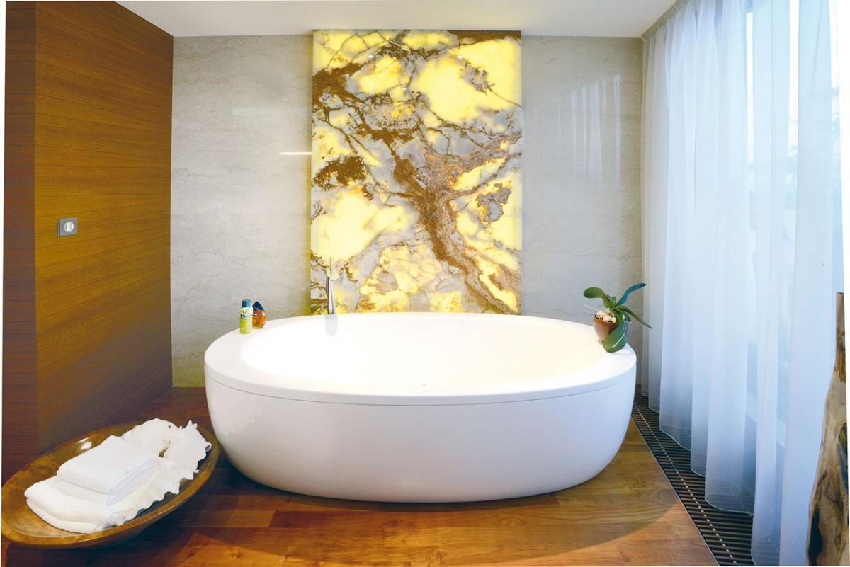 Na stěnách se dřevo střídá skamenným obkladem. Architekti si dali na výběru jednotlivých tabulí záležet – na větších plochách kresba žil navazuje tak, aby vznikl efekt jediného kusu kamene.