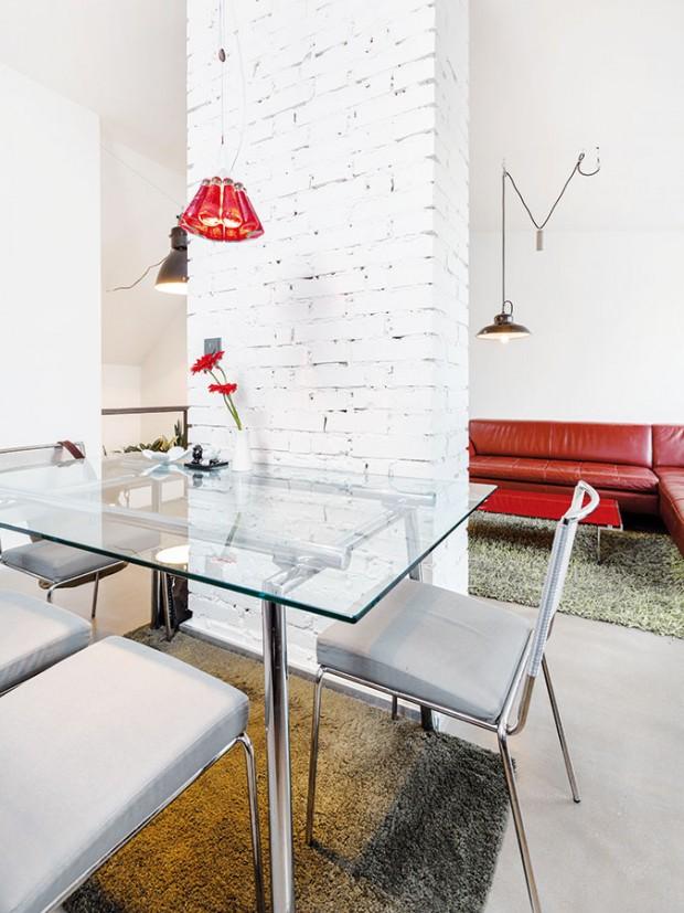 Vtipné designové svítidlo od Ingo Maurera je jedním zmála výrazných barevných akcentů vinteriéru. Skleněný jídelní stůl sežidlemi – stejně jako koženou sedačku – si Radek přinesl zpředchozího bydlení. FOTO DANO VESELSKÝ