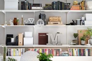 Jednoduchá konstrukce police je doplněna bílými regály, na které se vejde vše potřebné – od knih, přes květináče s rostlinami a památkové předměty až po dekorace či elektroniku. Foto: Alvhem