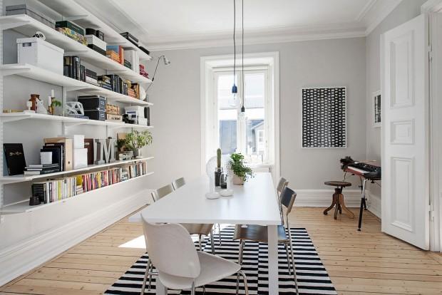 Světle šedá stěny doplňují bílý strop a dřevěnou podlahu. Monochromatický koberec ladí s grafikou na stěně a místo se našlo i pro klávesový hudební nástroj. Foto: Alvhem