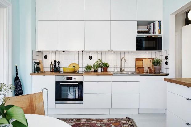 Jednoduchá kuchyňská linka doplněná dřevěnou pracovní deskou a bílou kachlíkovou zástěnou nabízí skutečně štědrý úložný prostor, který dokonale zapadá do prostoru. Foto: Alvhem