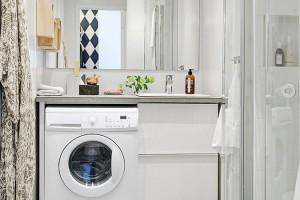 Malá koupelna je vyřešena co nejpraktičtějším způsobem. Jednoduchá sestava byla v roce 2013 stvořena z umyvadla, skříňky, betonového pultu a pračky a je umístěna pod velkým zrcadlem; sprcha a WC jsou napravo. Foto: Alvhem