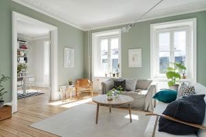 Velký obývací pokoj má světle zelené stěny a je zařízená velmi jednoduše. Poutavým prvkem jsou polštáře s různým vzorováním, které vhodně doplňují světlý nábytek a koberec. Foto: Alvhem