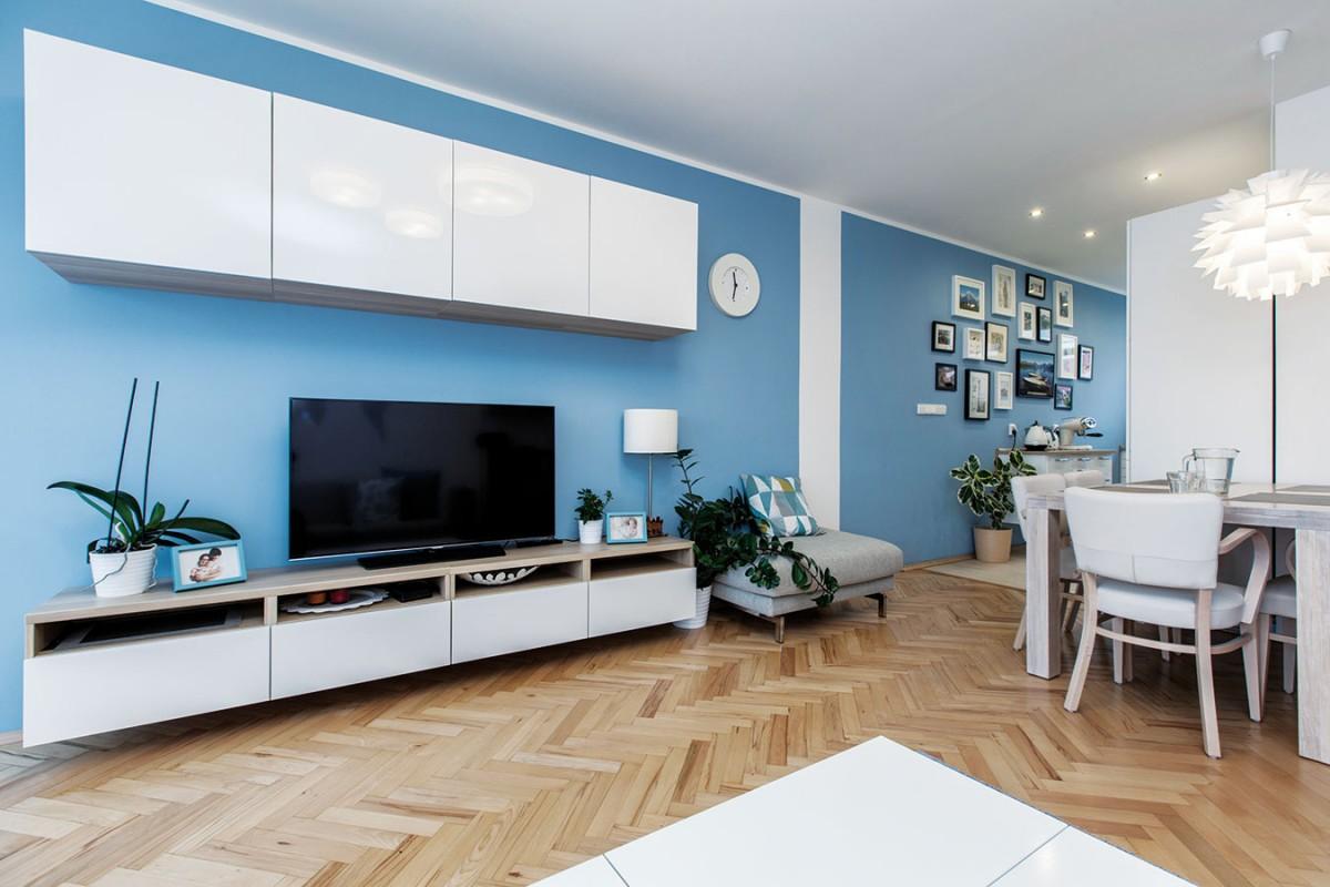 Kuchyňská aobývací část jsou opticky odděleny pomocí bílého pruhu na stěně, který půlí dvě modré plochy. Jde ojednoduchý, apřitom efektní trik. FOTO DANO VESELSKÝ