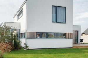 Svoji dřevěnou podstatu dům přiznává jen vdetailech částečného obložení na úrovni oken. FOTO MARTIN ZEMAN / PRODESI