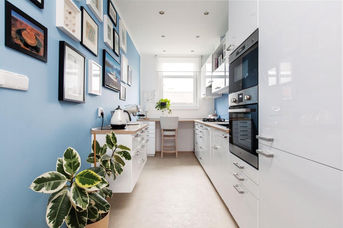 Kuchyňská linka je jednoduchá a praktická, kombinace bílých skříněk a světlého dřeva na desce působí nadčasově. Strohost rozbíjí doplňky a modrá mozaika na stěně za linkou. FOTO DANO VESELSKÝ