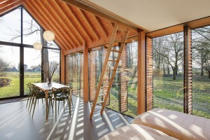 Jednolitý interiér je v přední, obývací části otevřený až do krovu. Působí tak velmi vzdušně, ale díky použití dřeva zároveň útulně. FOTO STIJN POELSTRA